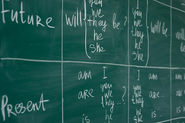 Image of a chalkboard with tables broken out for syntax analysis, display the English language future and present tense for the verb to be. Syntax analysis is one of the expertise included in CloudFactory's Natural Language Processing services.