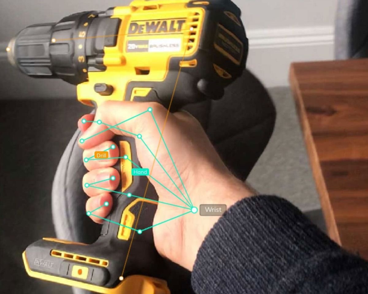 """This is an example of image annotation for computer vision using a wireframe. The image shows a person's right hand holding a cordless drilling tool, which is labeled with the word """"drill."""" There are points that indicate the pose points of the person's hand, with a point labeled """"wrist,"""" connecting to five other points to represent the position of the person's fingers, which are labeled """"fingers."""" Source: V7 Labs using Darwin, its data annotation tool."""